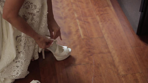 The bride wears white wedding shoes with her hands Footage