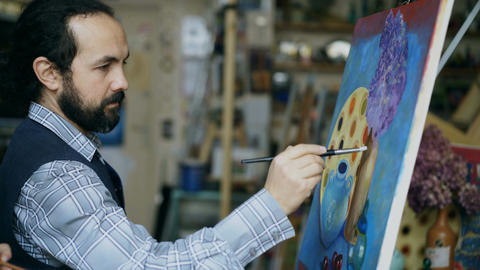 Concentrated man artist painting still life picture on canvas in art studio Footage