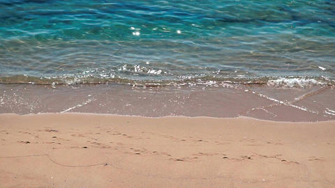 Turquoise colourful Aegean sea water waves breaking gently on a sandy beach Footage