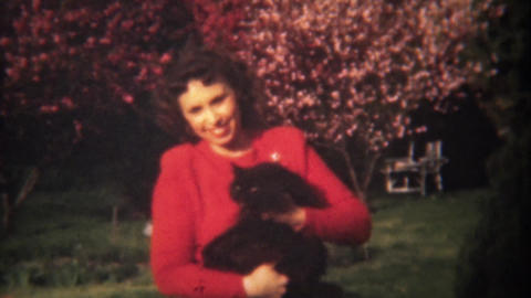 1948: Lady in red petting black cat spring flowering tree blossoms Footage