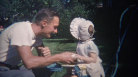 1948: Greaser style man entices uninterested baby with duck toy Footage