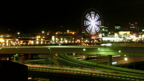 Elevated nightlapse of illumination over the highway junction and ferris wheel ビデオ