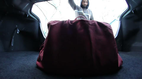 man pulls out a suitcase from the trunk and close Footage