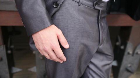 groom in grey wedding suit puts his finger into pocket Footage
