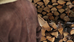 Man putting log on pile of stacked firewood Footage