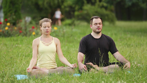 A man and a woman meditate in bliss. Young yoga instructors practice in a city Footage