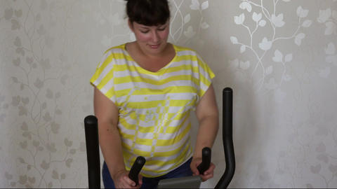 overweight woman exercising on trainer ellipsoid Footage