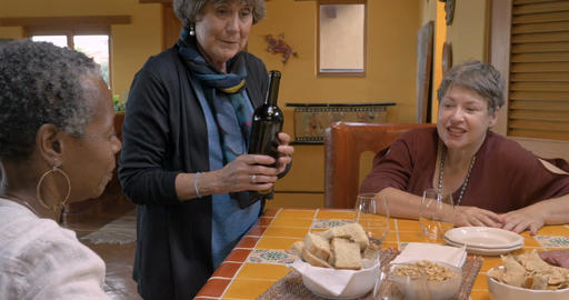 Elderly woman pouring wine for her mixed racial friends over 50 while they talk Footage