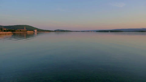 View of town Pasman in Croatia. Still sea water at early morning sunrise. In Footage