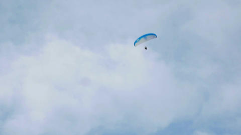 Paraglider flying on cloudy windy day risking and testing his luck. Flying high Footage