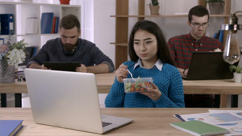 Asian businesswoman eating salad at desk in office ビデオ