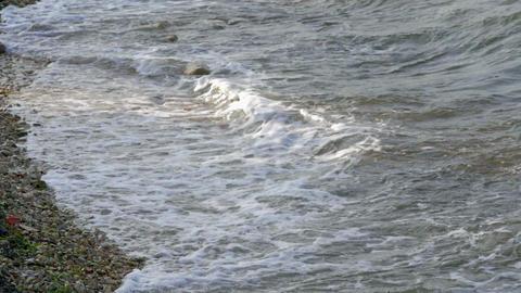 waves splashing on sandy beach in slow-motion hd. Last sun rays shining on wave Footage