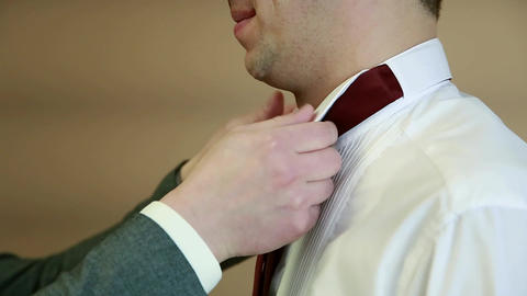 The witness helps the groom to wear a burgundy tie Footage