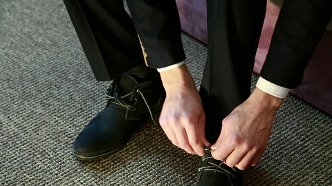 The groom knits his shoelaces on his shoes Footage