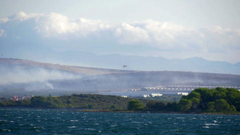 Forest fire with lots of smoke at Croatian coastline next to the town of Bild