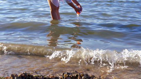 mother washing babies swimwear in sea water at beach. when done she walks out of Footage