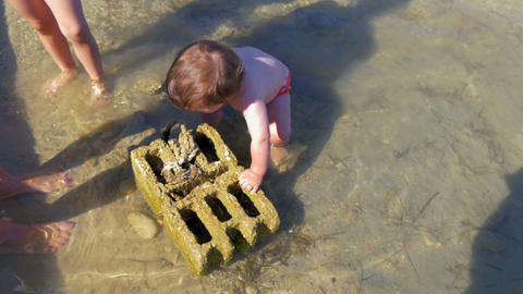 baby boy exploring concreete block laying in shallow sea water. in slow-motion Footage