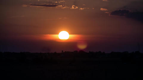 A time lapse of the large orange sunset as the massive sun sets into the horizon Footage