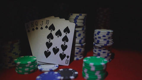 Royal flush on cards and poker chips on red casino table Live Action