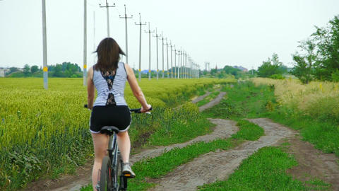 woman rides a bicycle through the fields on the nature Footage