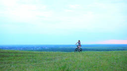 girl rides a bicycle on a background of nature clouds sky Footage