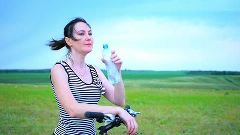 Young girl is drinking mineral water,Portrait of a young girl drinking water Footage