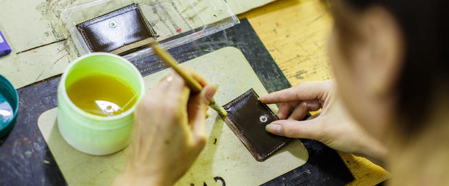 woman smearing with glue a part of a wallet Photo