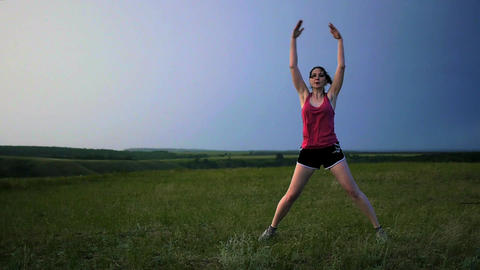 athlete warming up doing jumping exercises running on a sunset background for Footage
