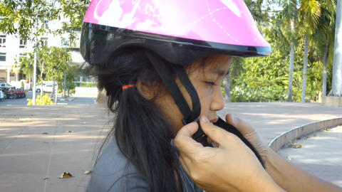 Mother hands wearing safty helmet to cute Asian little girl Archivo