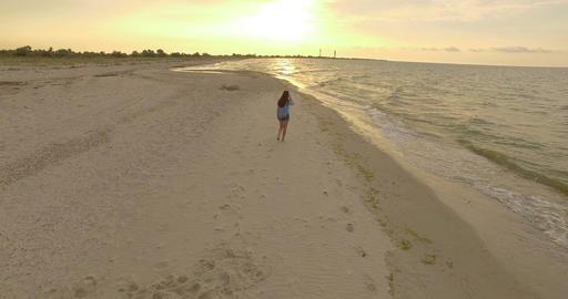 4k aerial - Beautiful Girl Walks Along a Sandy Beach at sunset Footage