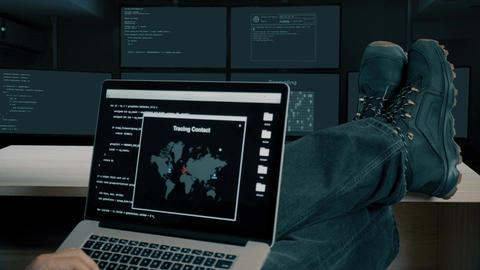 Hacker feet up to table. Hacker with laptop coding exploit to crack code Live Action