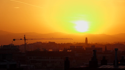 Tower crane jib against vivid sunset over city and mountains tops on horizon Footage