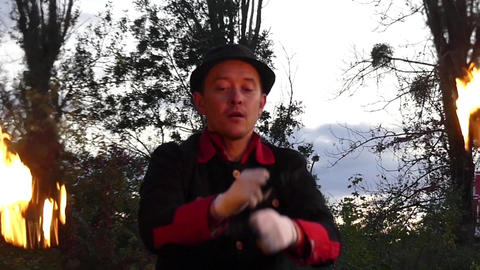 Magician Turns Two Balls of Fire Outdoors in a Forest in Autumn in Slo-Mo Footage