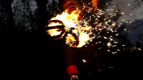 Fire Man Twists Two Lit Balls of Fire Around Himself Outdoors in Slo-Mo Footage