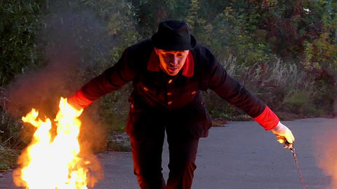 Magician Turns Two Ball of Fire Close to The Land in a Forest in Slo-Mo Footage