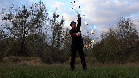 Fire Juggler Twists Two Lit Fans Around Himself Outdoors in Slo-Mo in Autumn Footage
