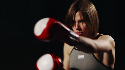 Brunette in sport suit and Boxing gloves on a black background conducts training Footage