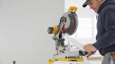 man cutting shoe Moulding on electric saw Archivo