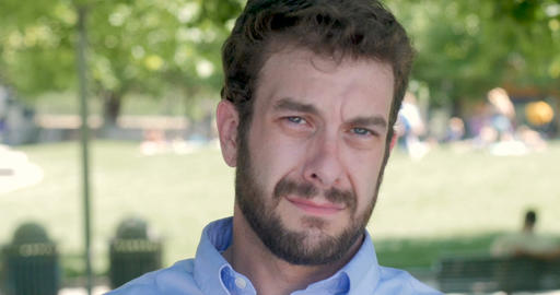 Upset handsome man with a short trimmed beard in early 30s holding back tears of Footage