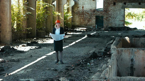 architect builder engineer builder of ruined building looking girl work plan for Live Action