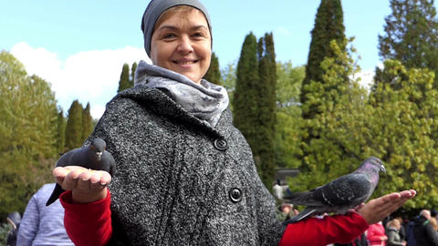 A happy woman feeding several doves from her hands in slo-mo Footage