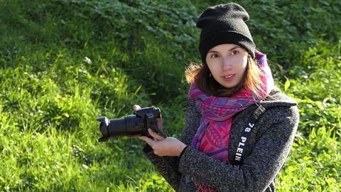 An attractive woman looks at her camera screen on a lawn Footage