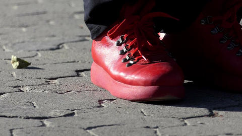 Red boots make dancing pas on a tiled sidewalk in slo-mo Footage