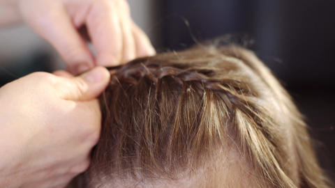 An attractive woman does her hairstyle for her little daughter. A woman plaits a Footage