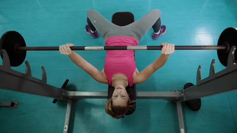 the girl lying on the bench raises the bar from her chest. Bench press from the Live Action