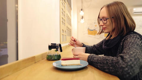 Сheerful girl enjoys a hot drink with dessert sitting in the evening in a cafe Footage