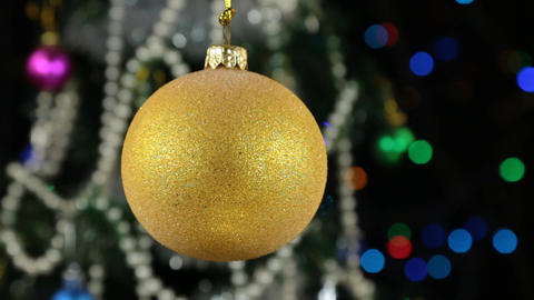 Beautiful yellow New Year and Christmas decoration ball swinging on rope Footage