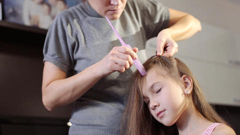 A pretty woman plaits the braid of her little daughter. Braiding the braids on Filmmaterial