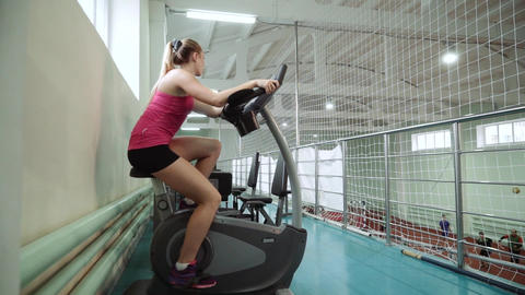 Beautiful girl in a gym exercising on a stationary bike Footage