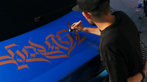 Upper View Artist Paints Beautiful Gold Patterns on Blue Live Action